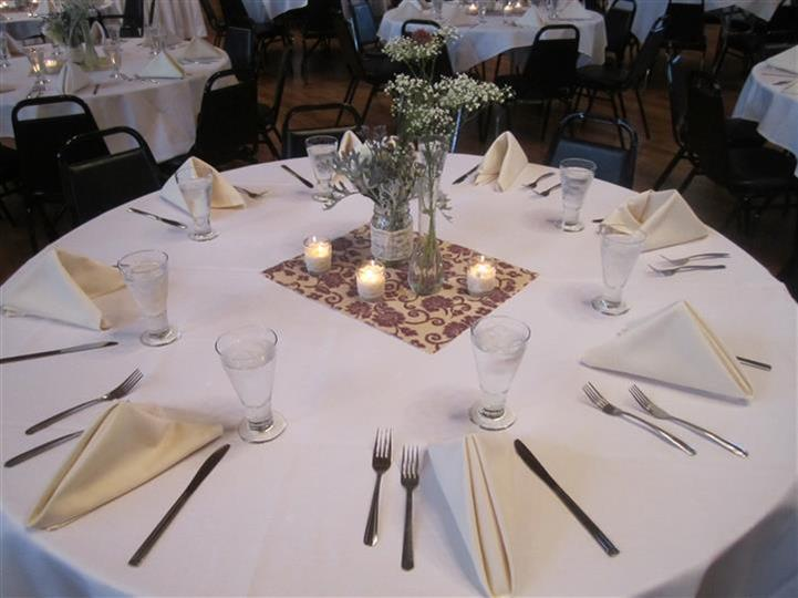 round table with napkins, silverware, glasses and center piece