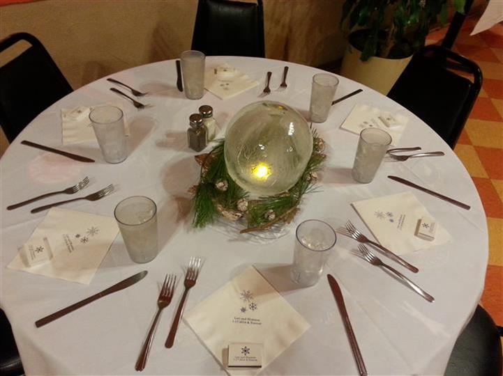 round table with napkins, glasses, silverware and lighted candle in the middle