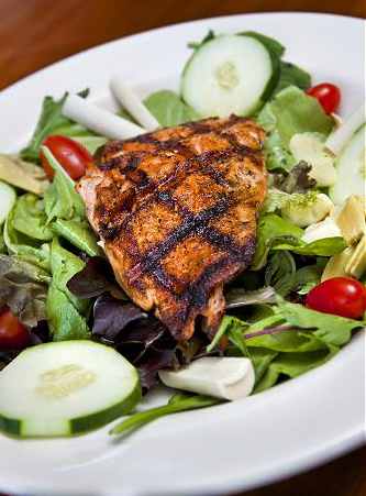 piece of blackened chicken over a salad with cucumbers and tomatoes