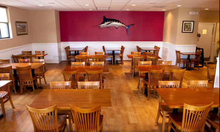 Dining room with brown wood tables and chairs.  Mounted swordfish on red wall in background.