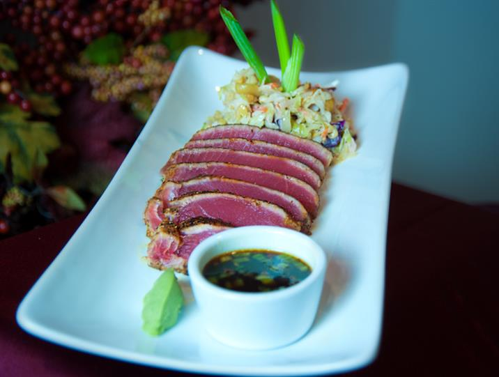 Ahi tuna with asian slaw and wasabi dipping sauce on white plate