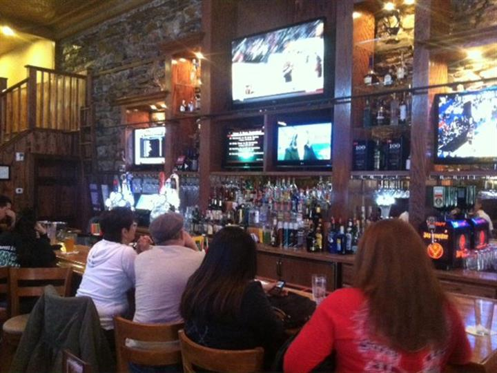 Patrons watching sports on TV at bar