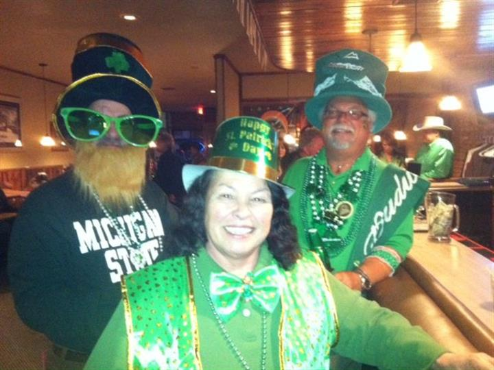 Patrons posing for photograph wearing saint patricks day attire.