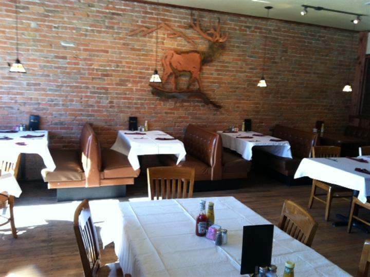 Dining tables with chairs and booths covered in white cloths