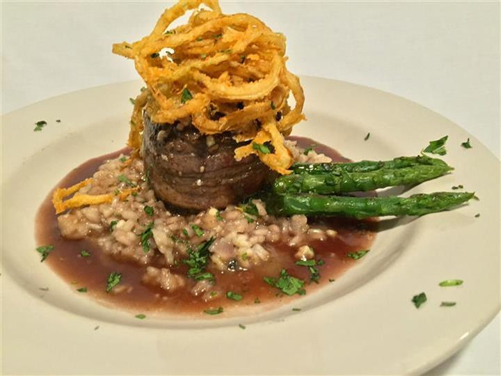 Bacon wrapped beef tenderloin over rice, topped with onion straws, side of asparagus.