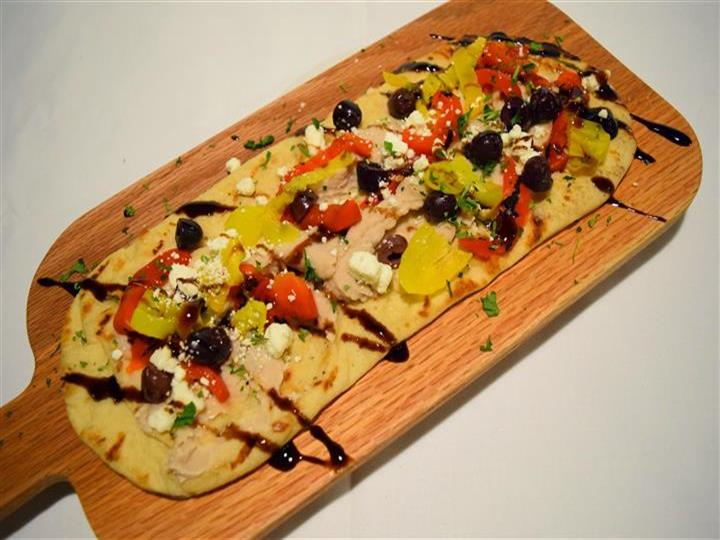 Flatbread pizza with chicken, pepperoncini, balsamic, feta cheese on wood board
