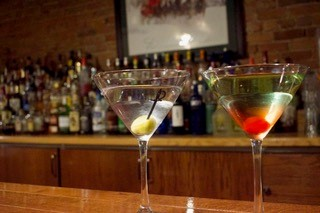 Two martinis sitting on bartop