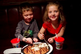 Young boy and young girl eating jumbo chocolate chip cookie. Baked in a cast iron skillet, served hot with two scoops of vanilla ice cream and chocolate syrup.