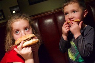 Young boy and young girl eating hamburgers in dining booth