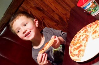 Young boy eating pizza in dining booth