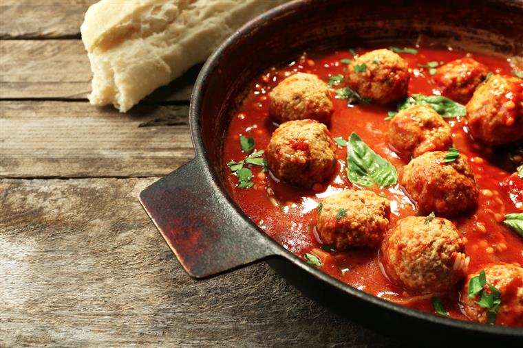 Bowl of red sauce and meatballs on wooden table next to loaf of bread