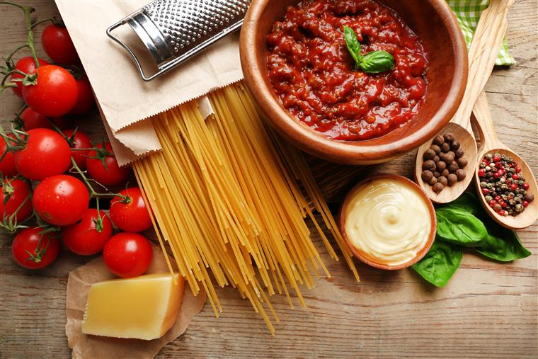 Uncooked spaghetti on wood table with tomatoes, bowl of red sauce, cheese grater, brick of cheese and spices