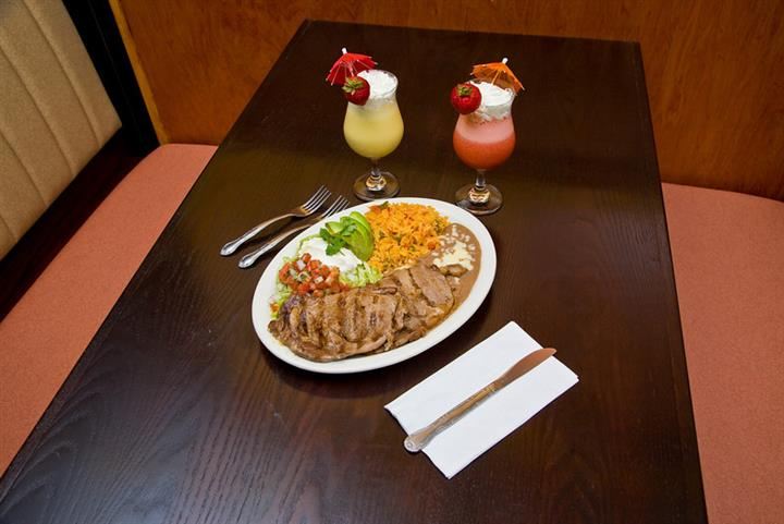 Mexican dish on plate of yellow rice with lettuce, tomatos, sour cream, and beans on a brown table with frozen drinks