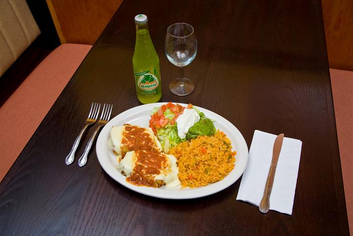 Mexican dish on plate of yellow rice with lettuce, tomatos, sour cream, and beans on a brown table with mexican sodas and frozen drinks