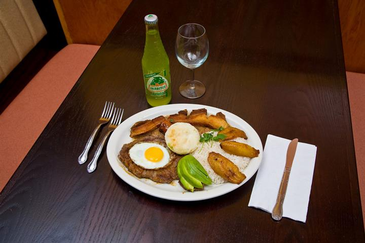 Plate of food with fried egg on top of meat next to rice and plantains on a brown table with greeb mexican soda