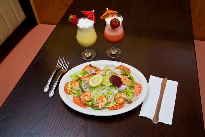 Salad with shrimp on brown table with two frozen cocktails