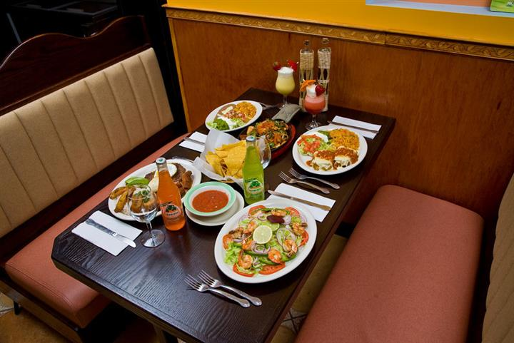 Four plates of food on a brown table with mexican sodas and frozen drinks
