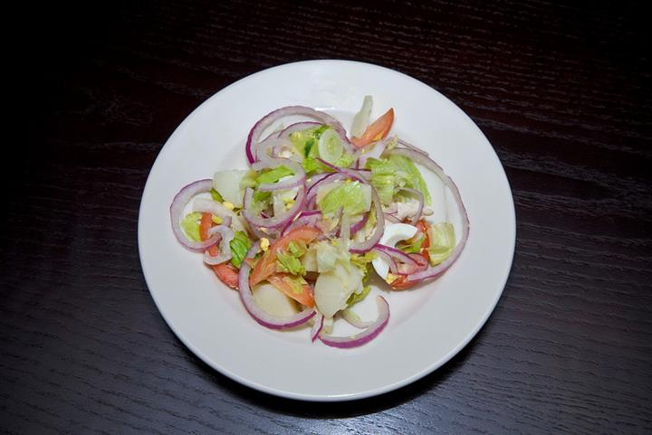 White plate with onions, lettuce and tomatos