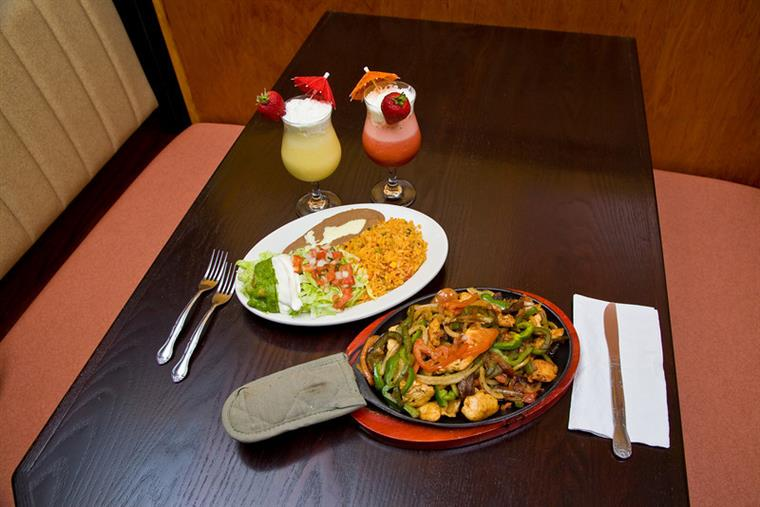 Fajitas and plate of yellow rice with lettuce, tomatos, sour cream, and beans on a brown table with mexican sodas and frozen drinks