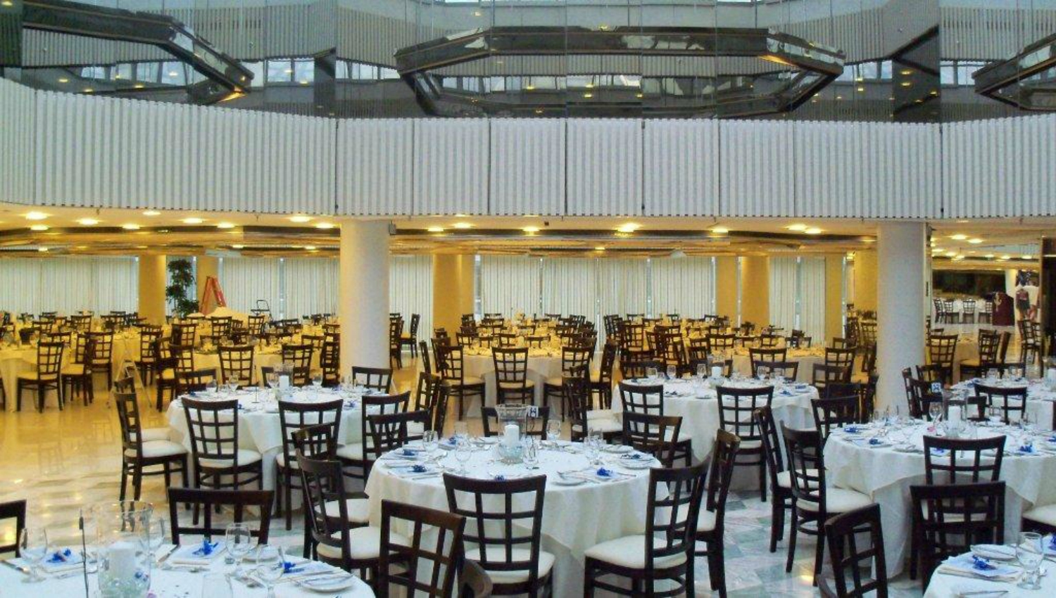 Multitude of white-clothed round tables and brown chairs in dining room