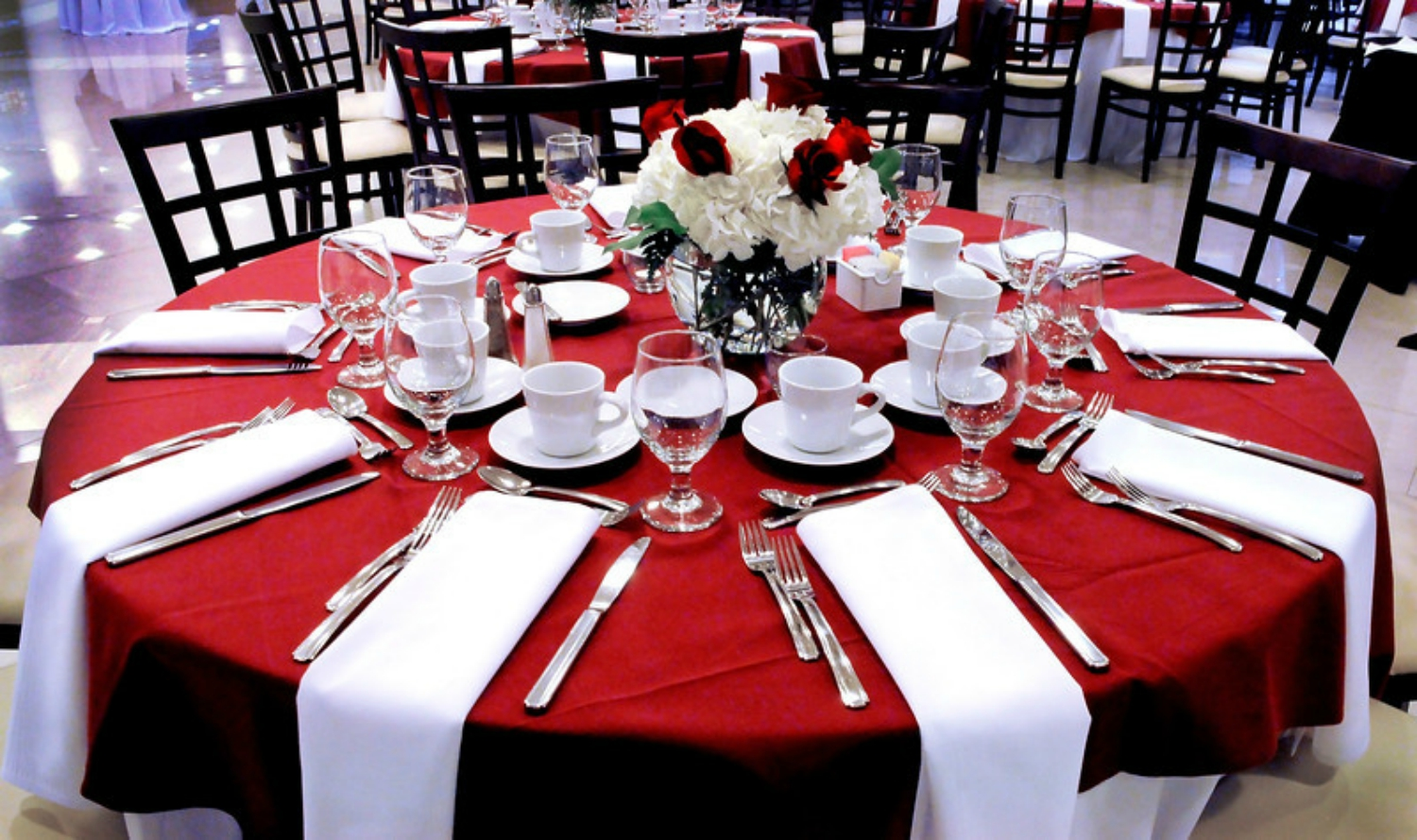 Room with round dining tables with red table cloths. White napkin placesettings and flower centerpieces.