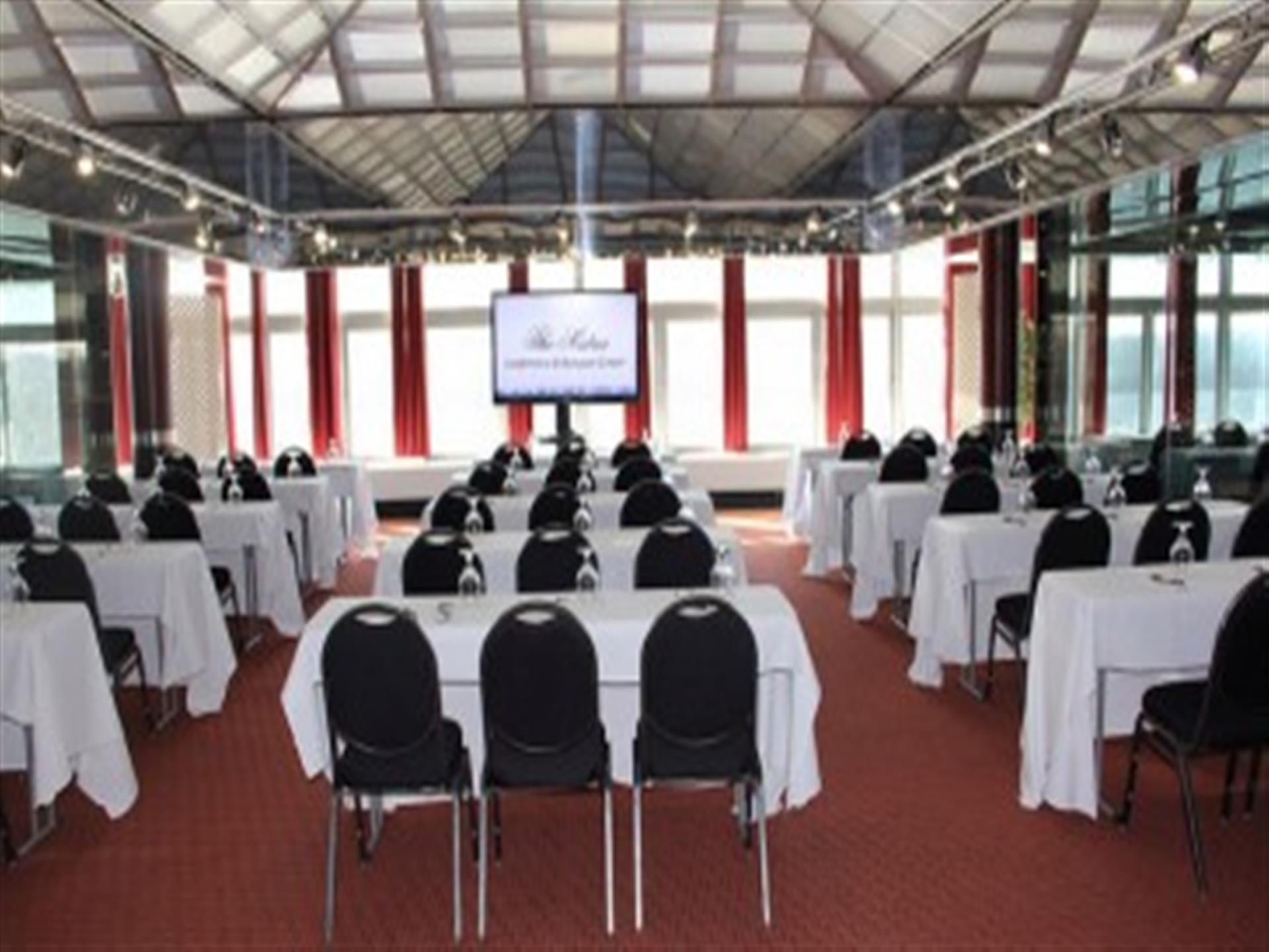 Conference room with white tables and black chairs. Room has red carpet and bright window.