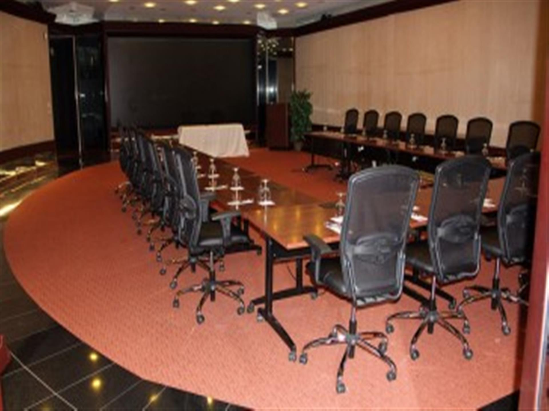 Boardroom with brown tables and black chairs