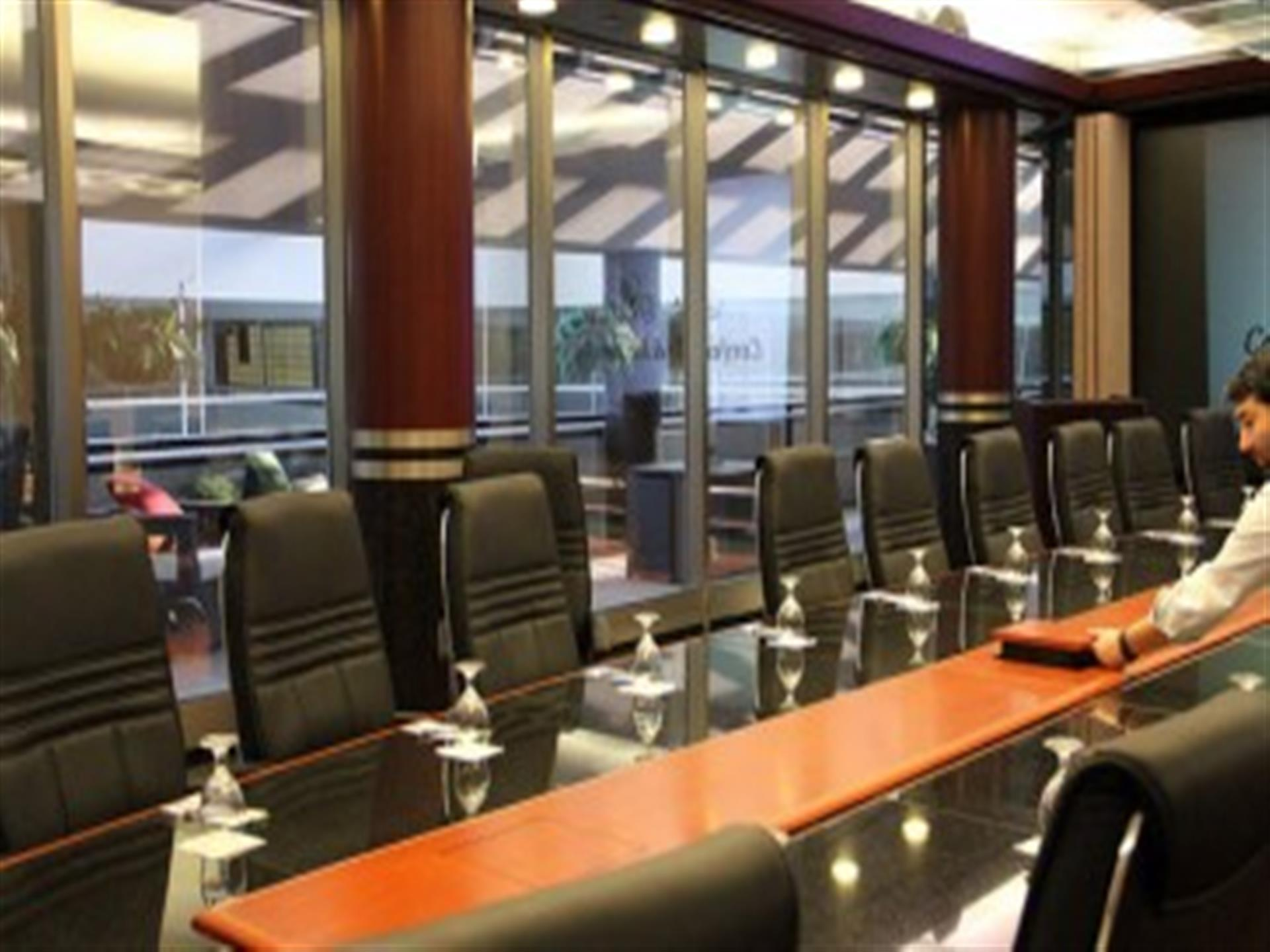 Executive boardroom table with chairs in front of window