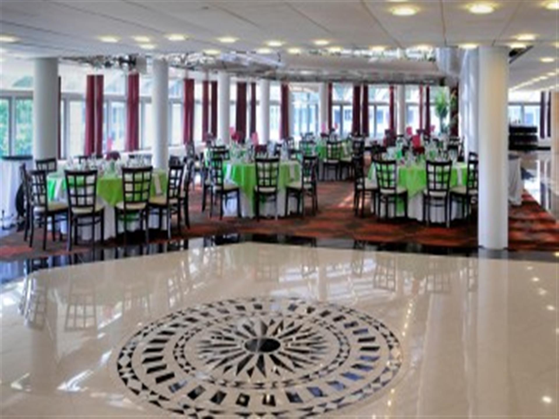 Dining hall with green-clothed tables and white trim. White placesettings. Brown and white chairs in front of windows. White tile floor in foreground.