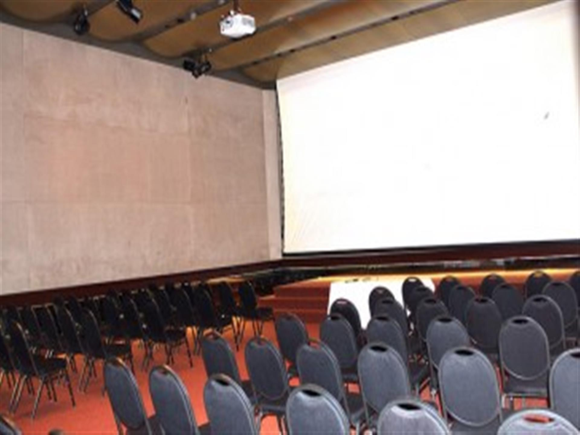 Conference room with rows of black chairs and large screen