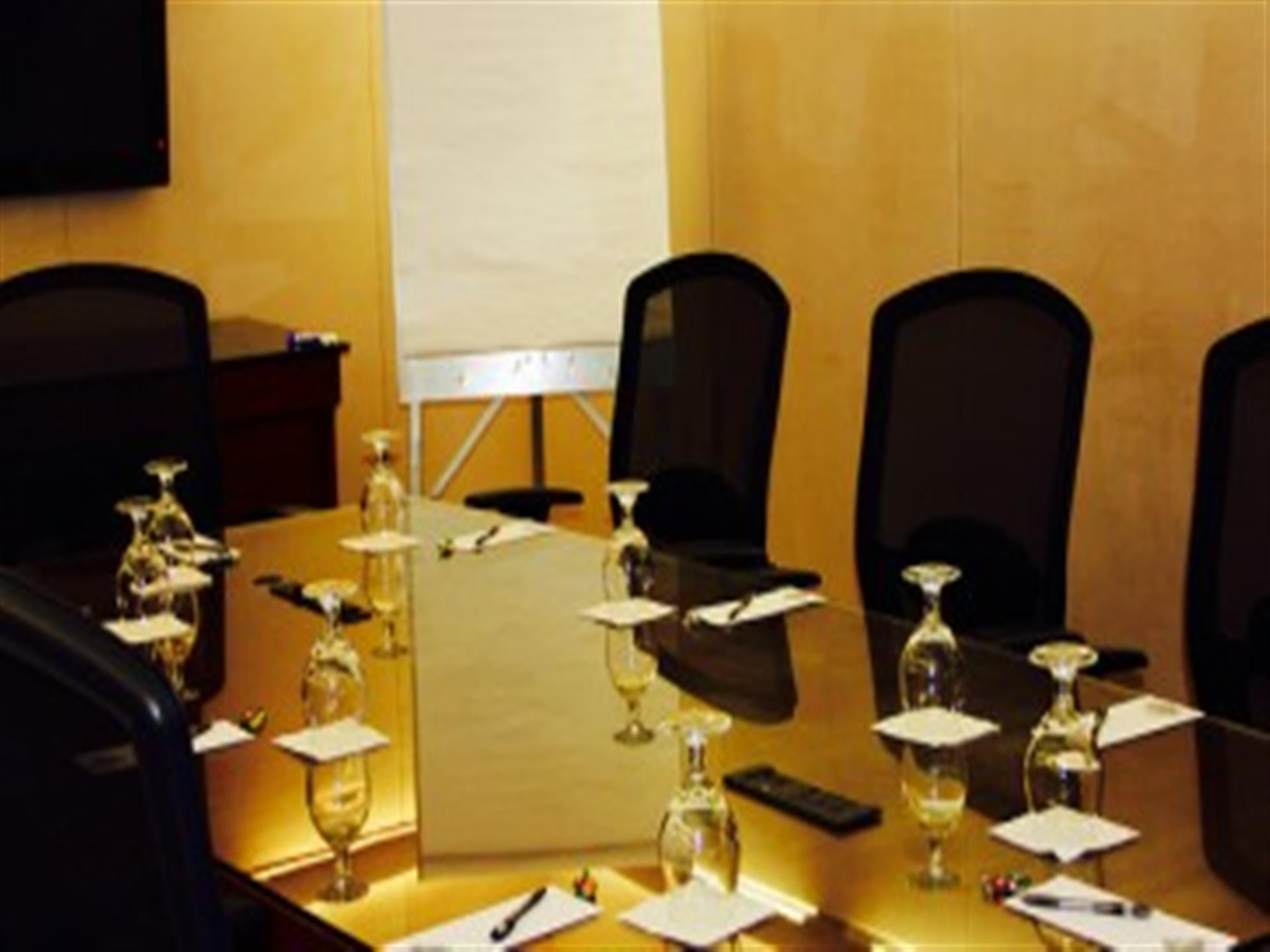 Conference room with glass-top table, surrounded by black mesh-back chairs