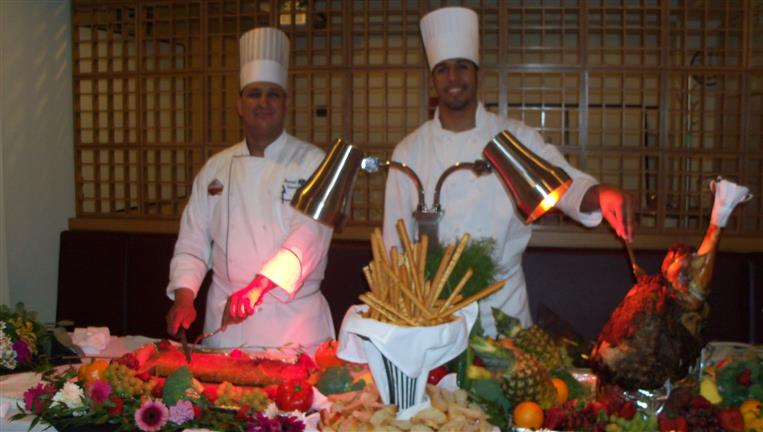Two chefs behind carving station.