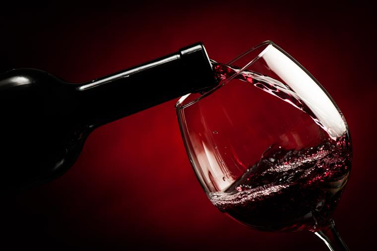 Red wine being poured in to glass against red backdrop