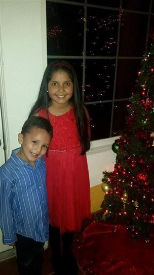 kids standing next to a christmas tree