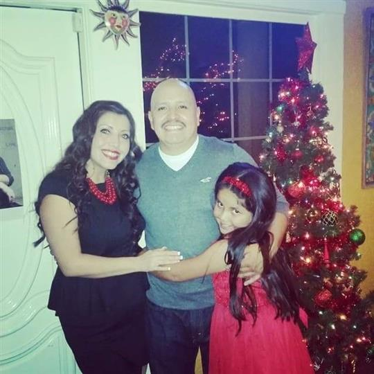 male, female, and young girl posing for picture with a christmas tree in the background