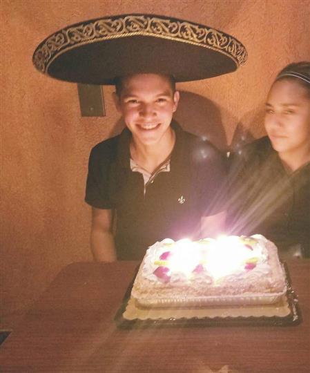 male wearing a hat smiling with a cake on the table