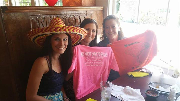three females posing for picture. one is wearing a hat, other two are holding up shirts