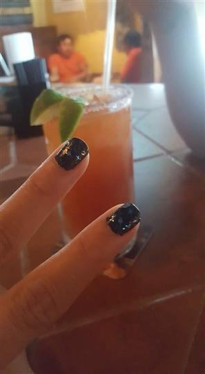 close-up of finger nails with a drink in the background