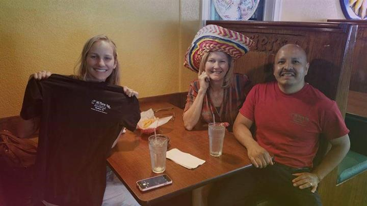 three people smiling sitting a a table. one person is wearing a hat