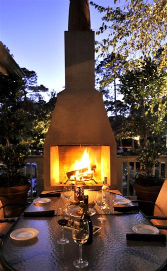 outdoor fireplace with table and 2 chairs in front