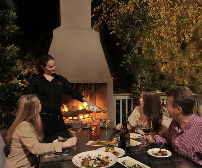 outdoor fireplace with table and 3 people sitting in the chairs looking at the waitress