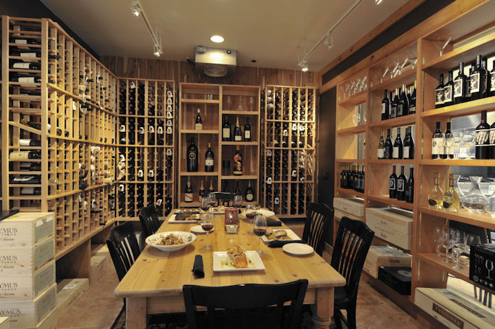inside a private room surrounded by wine bottles, with a large table, chairs and plates filled with food