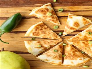 Quesadillas on wood cutting board, garnished with diced jalapenos