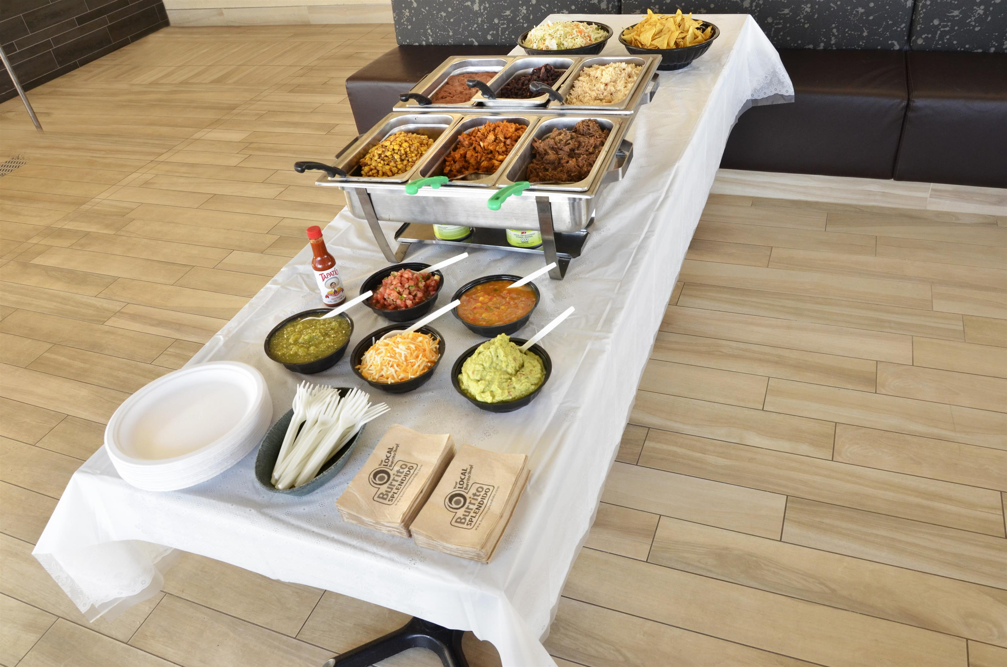 overhead view of warming trays on a table with plastic forks, napkins, plates and bowls filled with additional toppings