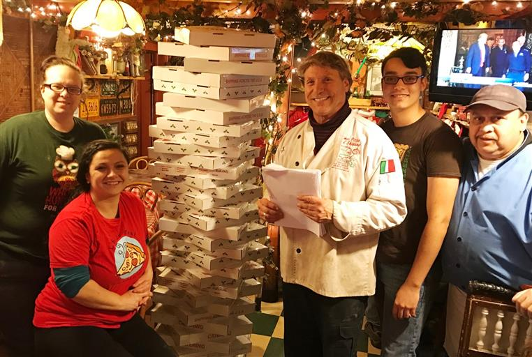 Prima Pizza family and staff posing near stacked pizza boxes.
