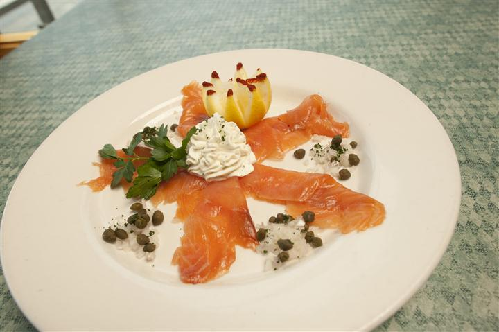 smoked salmon slices on a plate with capers and sauce