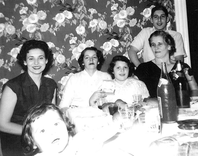 old black and white photo of a family sitting at the table
