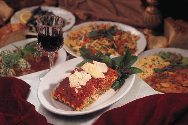 lasagna topped with cheese with a glass of wine. several other pasta meals on plates are in the background