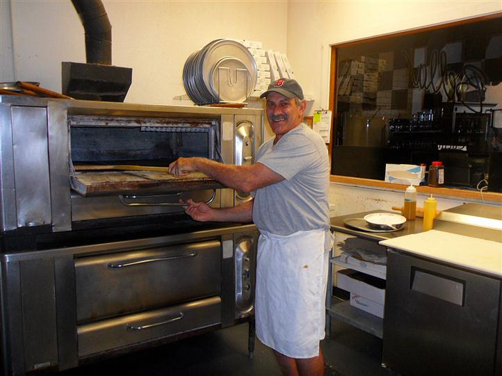 Anthony Roncarati getting pizza out of the oven