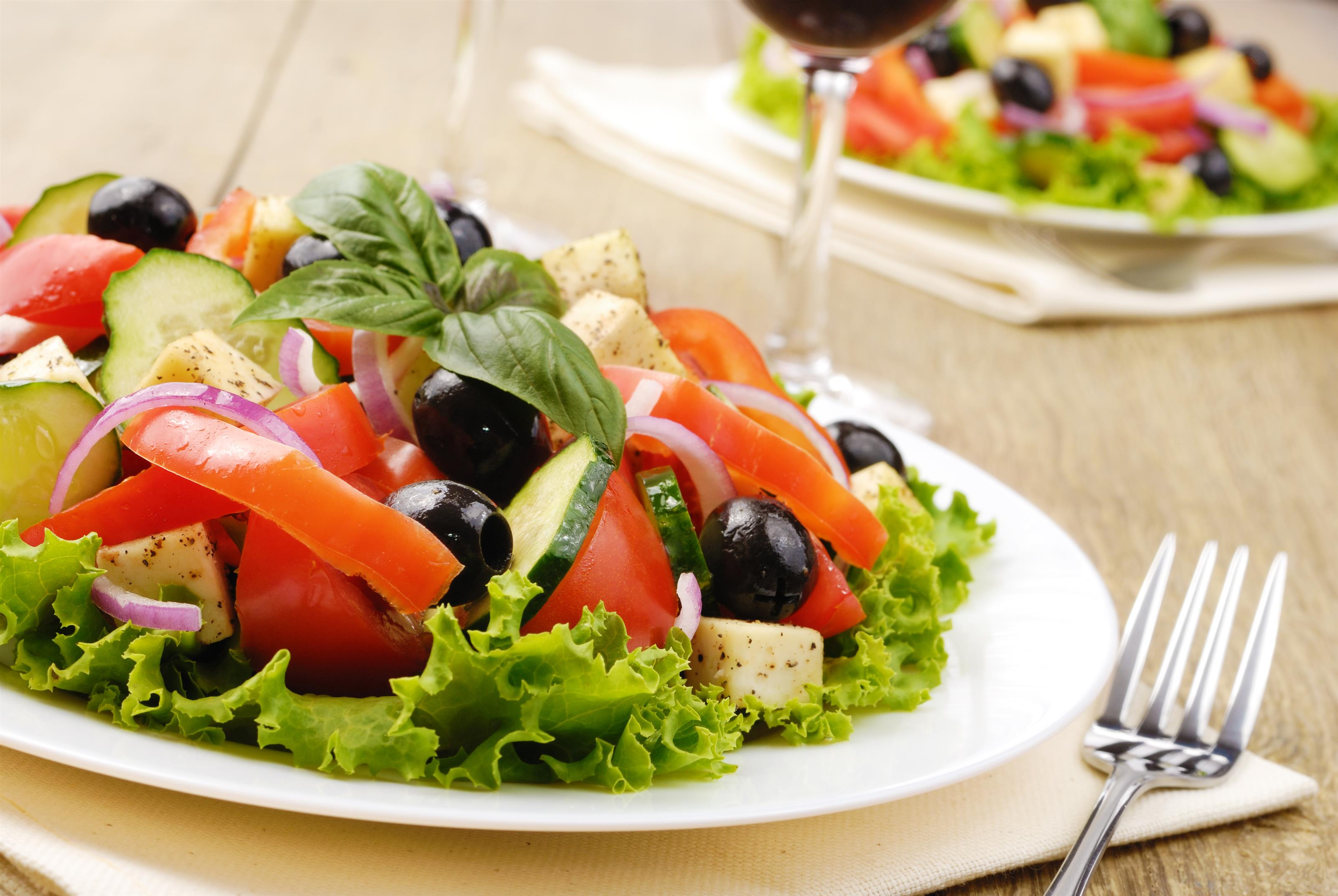 salad with a glass of wine and a fork